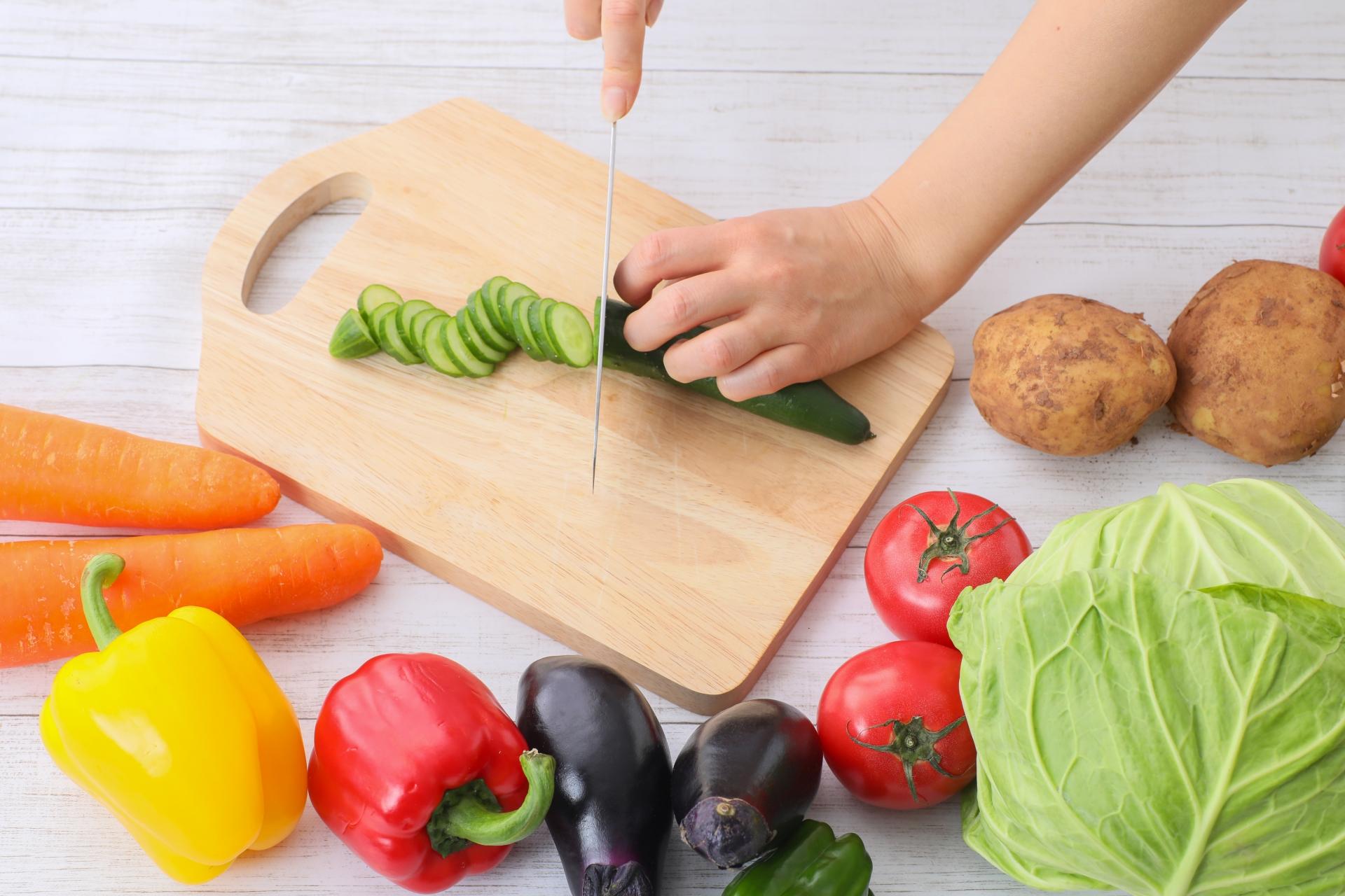 たくさんの野菜を切る女性の手