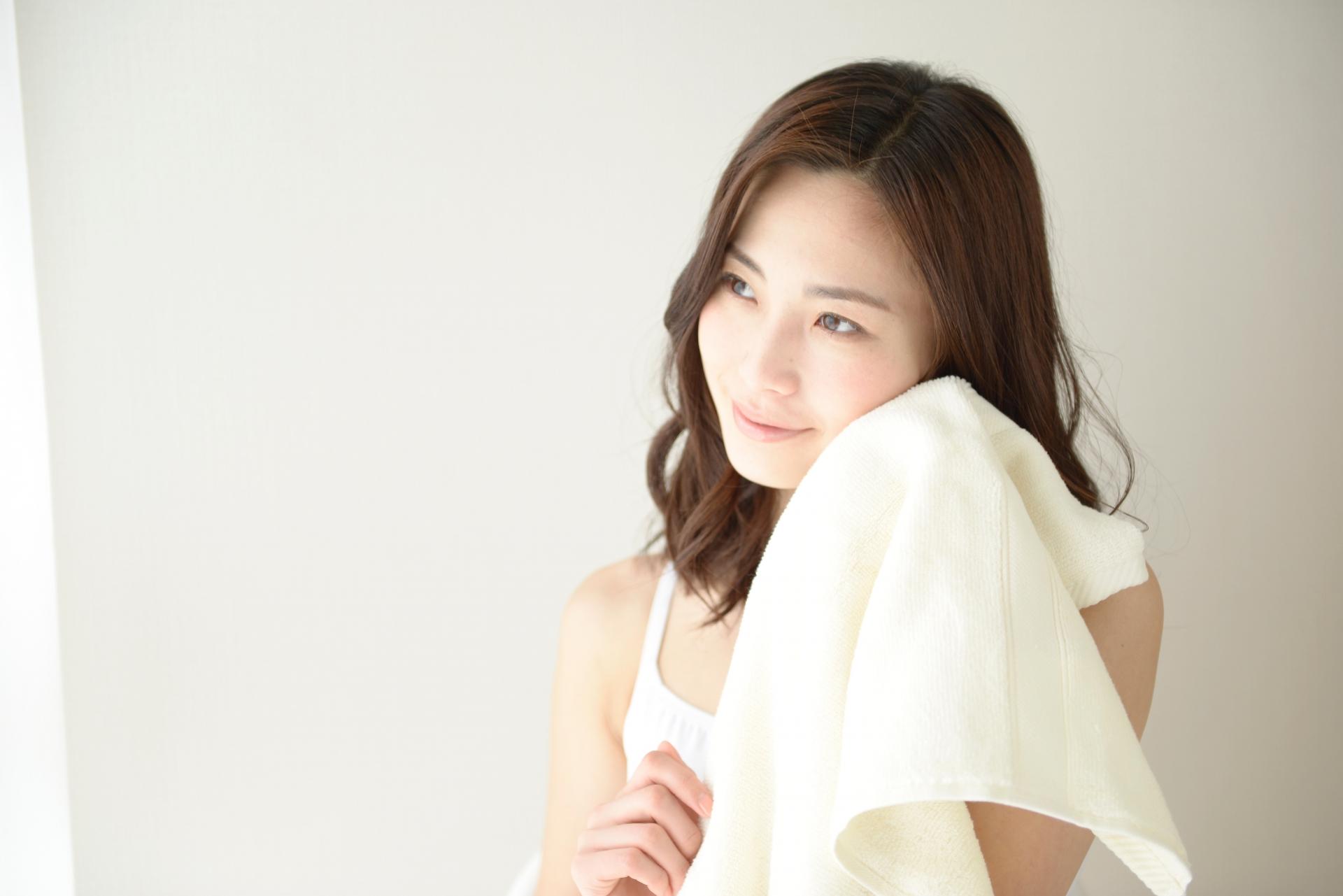 洗顔後タオルで優しく拭く女性