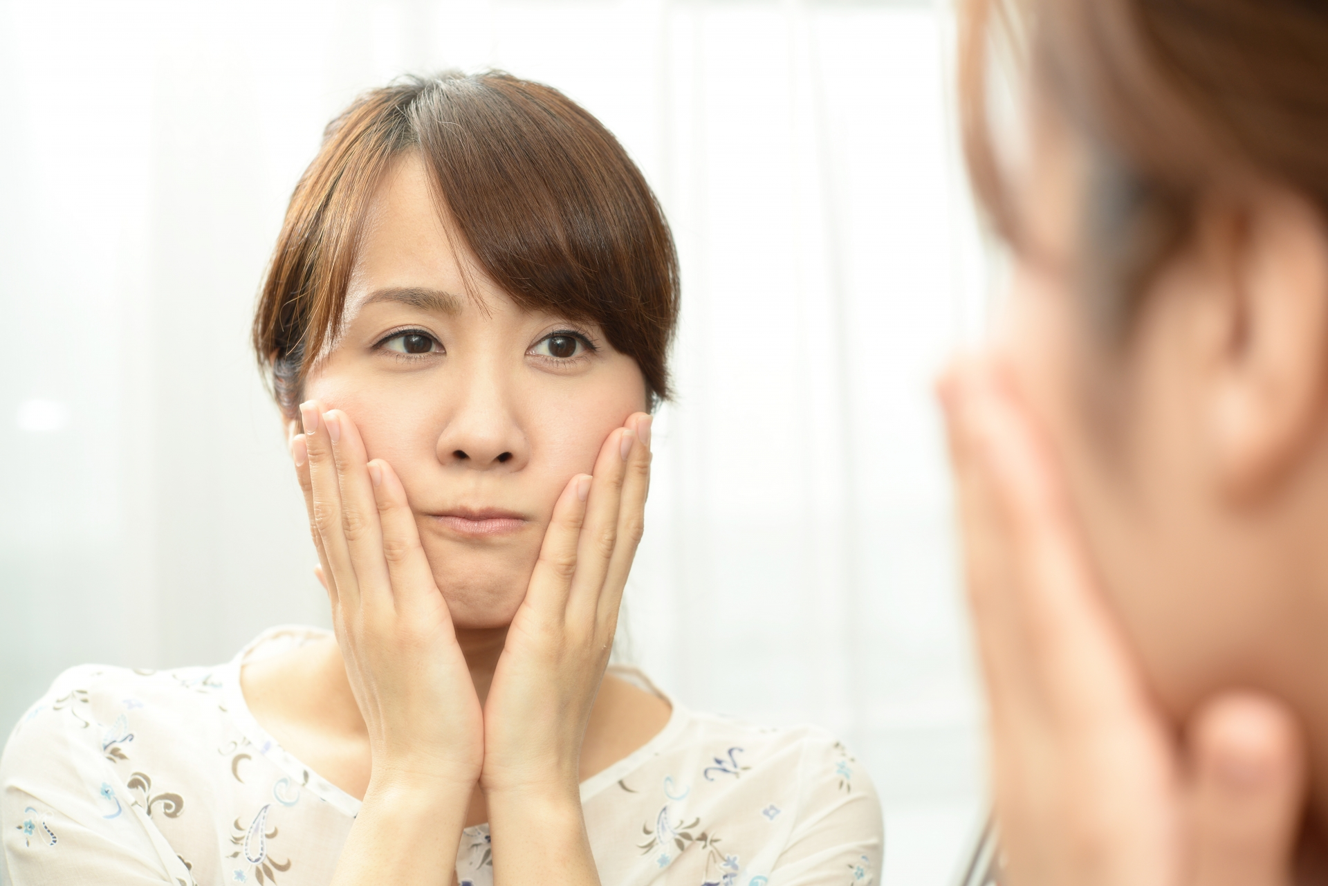 顔のテカリを気にするインナードライ肌の女性