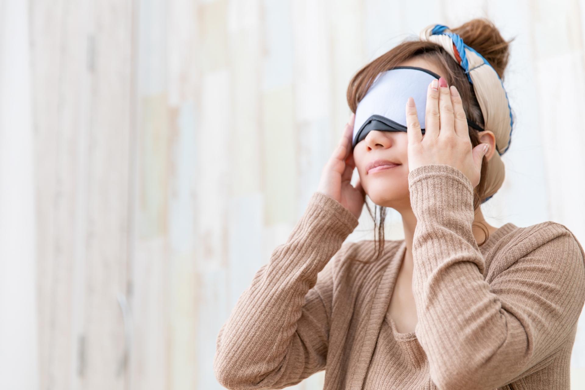 アイマスクで目をケアする女性